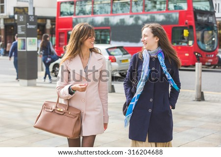 Two women are walking in London. They are friends and are having a great afternoon talking and laughing together. It's winter and both are wearing a coat. There is a typical red bus on the background - stock photo