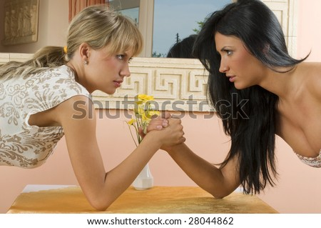 Two women arm wrestling at work on desk on white background - stock photo