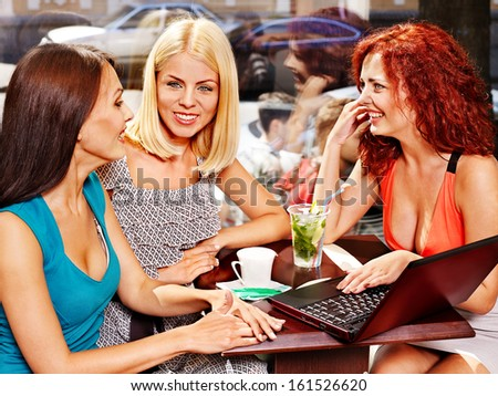 Two women at laptop drinking cocktail in a cafe.