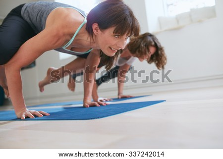 Two women at yoga class doing yoga hand stand pose. Mature woman standing on hands with feet lifted up doing crane yoga pose - Bakasana. - stock photo