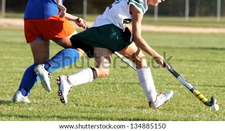 Two women battle for control of ball during field hockey game - stock photo