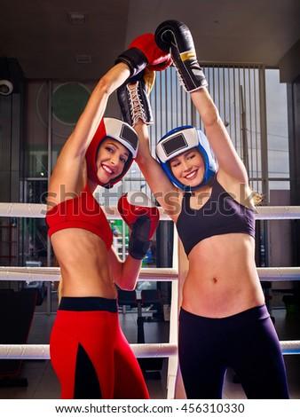 Two women boxer wearing gloves posing in boxer ring. Boxer women celebrating victory. - stock photo