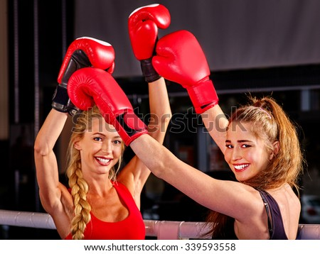 Two women boxer wearing red  gloves posing in ring hands up. - stock photo