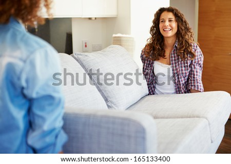 Two Women Carrying Sofa As They Move Into New Home - stock photo