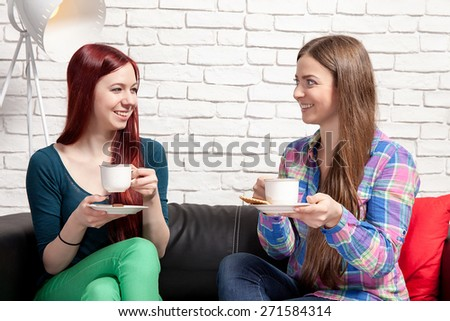 Two women chatting over coffee at home. - stock photo