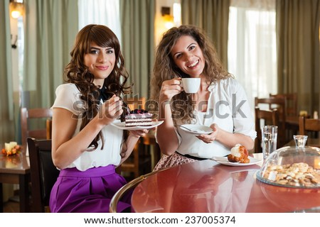 Two women chatting,smiling and having snack in caffee, enjoying a dessert, at the coffee / cake shop - stock photo