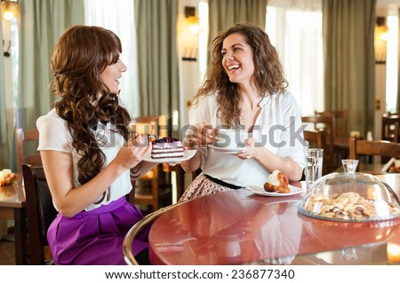 Two women chatting,smiling and having snack in coffee, enjoying a dessert, at the coffee / cake shop - stock photo