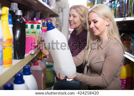 Two women choosing some detergents in the shop
