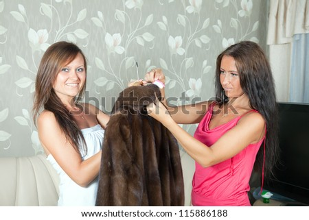 Two women cleaning fur coat  with whisk broom at home - stock photo