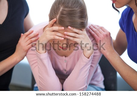 Two women comforting crying girl. Close up of crying girl, who covers her face with both hands  - stock photo