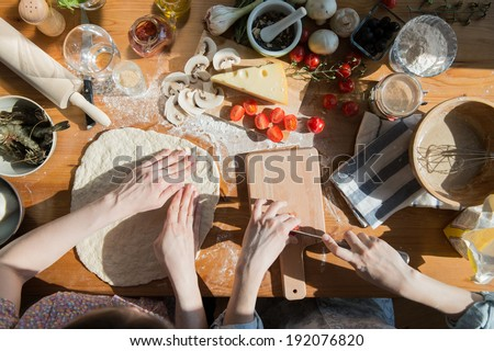 Two women cooking pizza at home. Filling pizza with ingredients. Top view. Overhead view. - stock photo