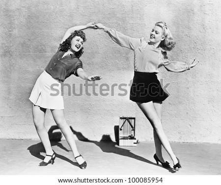 Two women dancing outside - stock photo