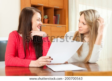 two women discussing a contract in the office