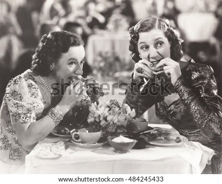 Two women distracted from their meal