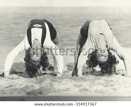 Two women doing backbends on the beach