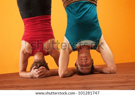 Two women doing headstands over yellow background