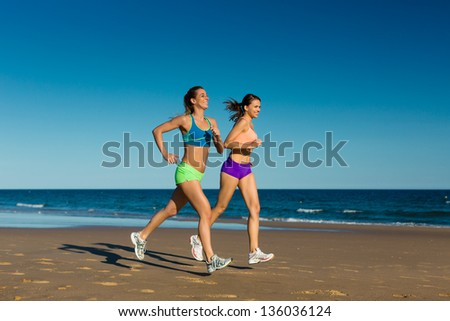 two women doing sport, jogging on the beach in their vacation on the sea - stock photo