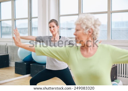 Two women doing stretching and aerobics workout at gym. Female trainer in background with senior woman in front during physical training session - stock photo