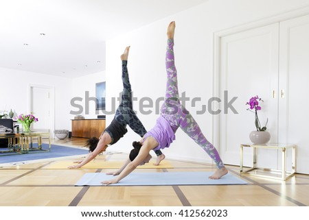 Two women doing yoga at home down dog split pose