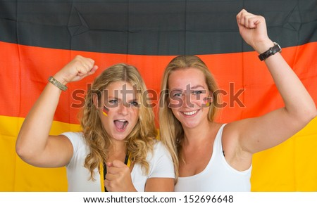 Two women, dressed in German team clothing, and with german flags painted on their cheeks, cheering on the Germany's national team in front of a German flag - stock photo