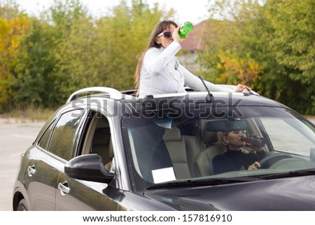 Two women drinking and driving both upending bottles to gulp down the alcohol with the passenger standing up through the sunroof - stock photo