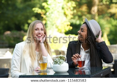 Two women drinking tea and socializing outdoors