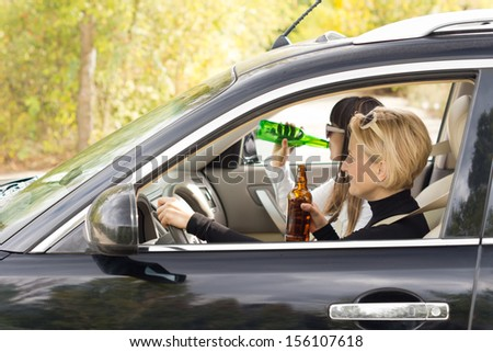 Two women driving a car on a rural road while drinking alcohol from the bottle in a case of dangerous driving - stock photo