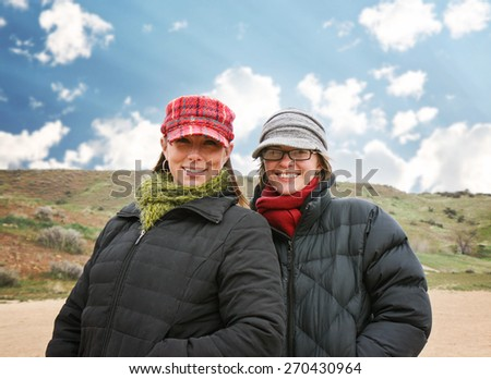 two women enjoying the outdoors on a brisk winter day at a local dog park - stock photo