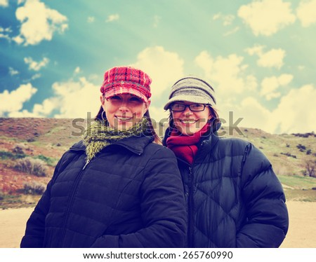 two women enjoying the outdoors on a brisk winter day toned with a retro vintage instagram filter effect app or action  - stock photo