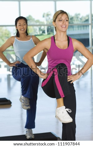 Two women exercising at a gym - stock photo