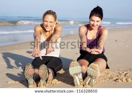 Two Women Exercising On Beach - stock photo