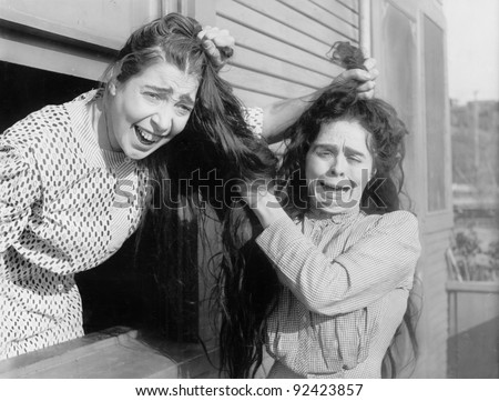 Two women fighting and pulling each other's hair - stock photo