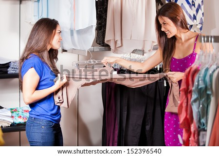 Two women fighting and pulling the same pair of pants for themselves