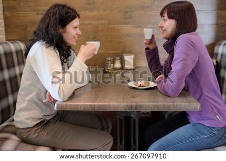 Two women friends talking in a cafe - stock photo