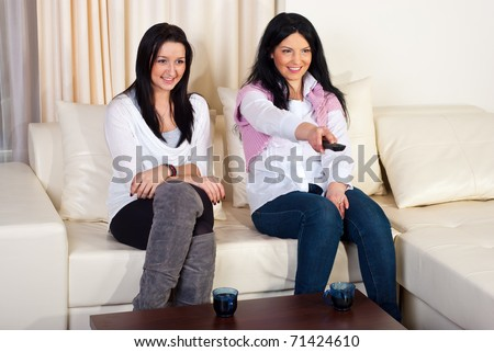 Two women friends watching tv and sitting comfortable on couch in a living room - stock photo