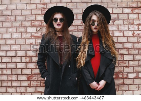 Two women friends wearing sunglasses and having fun. Happy girls in black coat and hats