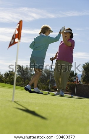 Two women giving high-five on golf course - stock photo