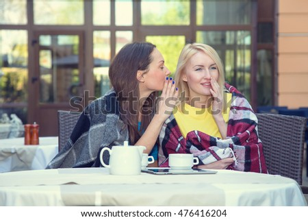 Two women gossiping at a meeting in a cafe. Discuss rumors.