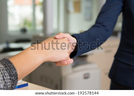 Two women greet each other with handshake in the office.