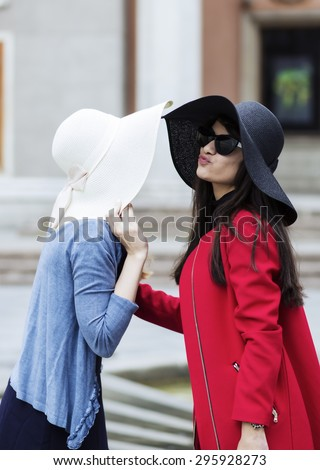 Two women greet each other with kiss