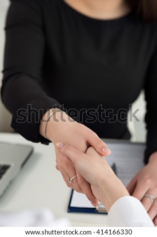 Two women handshake in office close up. Businesswomen shaking hands. Serious business, partnership and collaboration concept. Partners made deal and sealed it with handclasp. Formal greeting gesture - stock photo