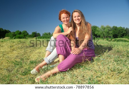 Two women have fun on top of hill in park - stock photo