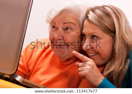 two women having fun with a laptop