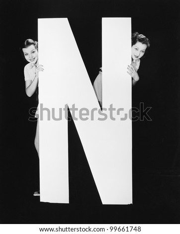 Two women hiding behind huge letter N - stock photo
