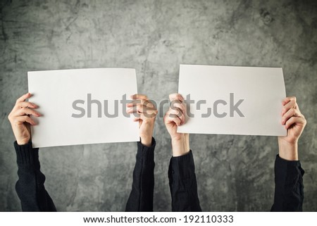 Two women holding blank paper posters above their heads