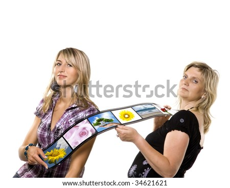 Two women holding film strip with color photos