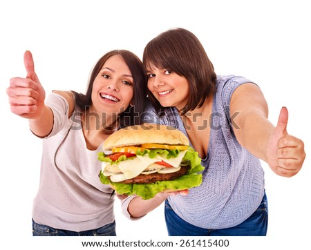 Two women holding hamburger and thumb up. Isolated.
