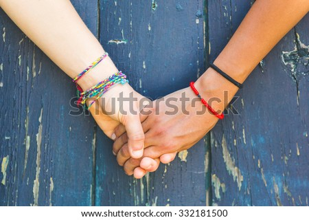 Two women holding hands with a wooden background. One is caucasian, the other is black. Multicultural, homosexual love and friendship concepts. - stock photo