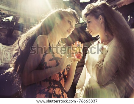 Two women holding magic flask - stock photo
