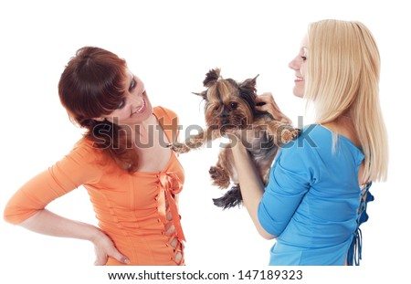 Two women holding their pet Yorkshire Terrier.